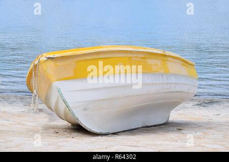 small abandoned wooden boat lies on the beach,the sea with shallow waves in the background - Stock Photo