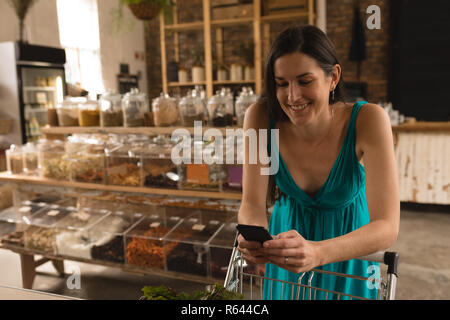 Woman using mobile phone while shopping in supermarket - Stock Photo