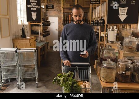 Man using mobile phone while shopping in supermarket - Stock Photo