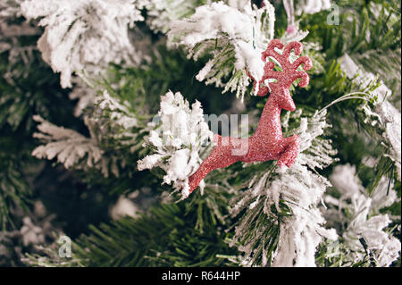 Christmas figure of red deer hanging on Christmas tree with snow - Stock Photo
