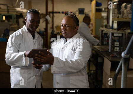Male workers discussing over a digital tablet in glass factory - Stock Photo