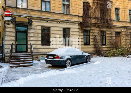 At the multi-storey yellow house on the roadside parked snow-covered car. - Stock Photo