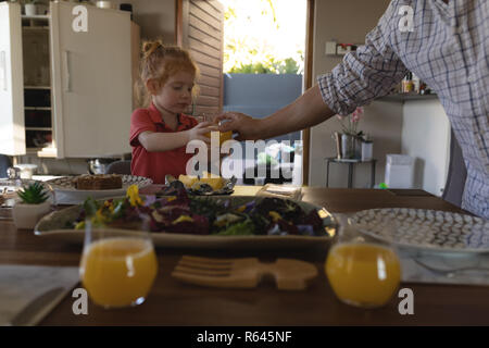 Father serving orange juice to his daughter on dining table - Stock Photo