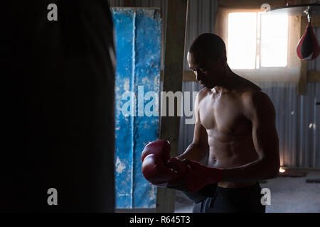 Male boxer standing with boxing gloves in boxing club - Stock Photo