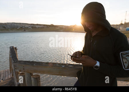 Male athlete using mobile phone on pier - Stock Photo