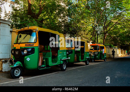 Three auto rickshaws parked on the side of the road waiting for commuters in Delhi, circa 2018. - Stock Photo