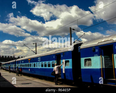 This is an Indian Railways train at Howrah station with a man checking the booking chart in Kolkata, India - Stock Photo
