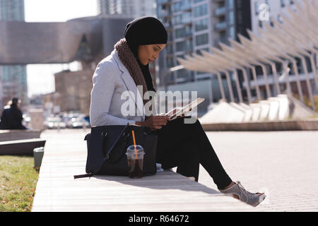 Woman using digital tablet in city - Stock Photo