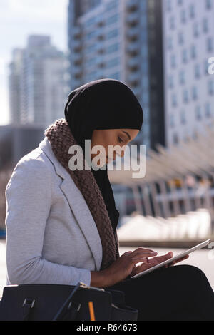 Hijab woman using digital tablet in city - Stock Photo
