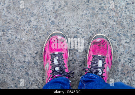 This is a top view of pink colored sports shoes with tied laces. the shoes are worn by a girl woman standing on a tarmac road also wearing blue jeans  - Stock Photo
