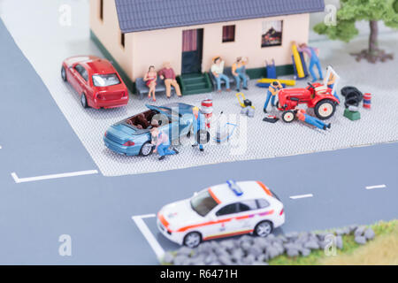 Miniature mechanics repairing a car and a tractor - Stock Photo