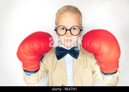 Cute little boy in a suit and bowtie wearing oversize boxing gloves and looking fearless while standing against a white background - Stock Photo
