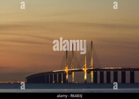 The bridge over Oresund between Copenhagen Denmark and Malmo Sweden in sunset. Copenhagen in the background - Stock Photo