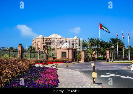 Abu Dhabi Emirates Palace Entrance with Waving Emirati Flags - Stock Photo