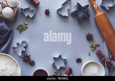 Cooking Christmas cookies. Ingredients for gingerbread dough: flour, eggs, sugar, cocoa, cinnamon sticks, anise stars and cookie cutters on gray woode - Stock Photo