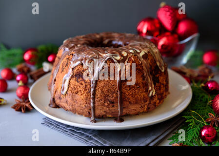 Christmas cake with chocolate icing on gray wooden background. Holiday decorations concept - Stock Photo