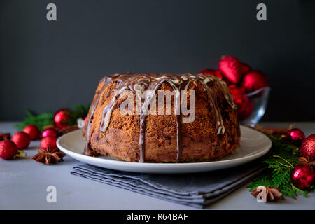 Christmas cake with chocolate icing on gray wooden background. Holiday decorations concept. Top view. Flat lay. Copy space - Stock Photo