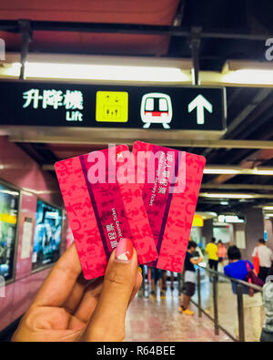 SINGAPORE - MAY 12, 2017: Woman holding EZ ticket and money on front Ticket Office of Singapore Mass Rapid Transit (MRT) In Changi International Airport - Stock Photo