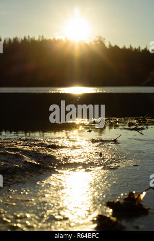 Newly risen sun is reflected on a partly frozen lake, creating a line of different sunlight. Sun visible at the top of the image. - Stock Photo