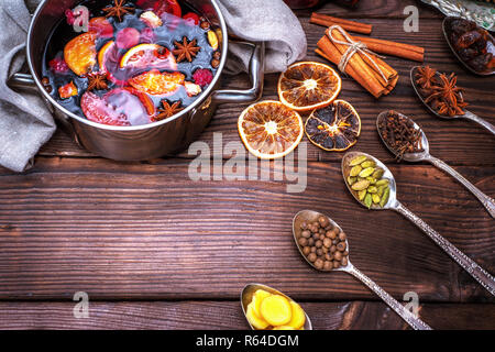 mulled wine in a saucepan and iron spoons with ingredients - Stock Photo
