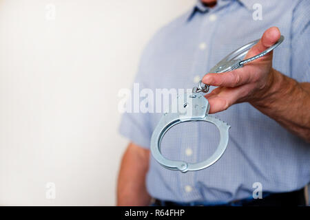 The man holds the handcuffs in his outstretched hand. Close up. - Stock Photo