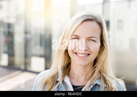 modern young business woman in casual look in front of glass building - Stock Photo
