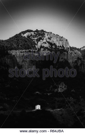 In the middle of the Sardinian mountain, a tinny farmer house shaded by a towering mountain. - Stock Photo