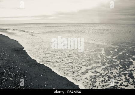 Empty beach scene, silvertone, monochrome, calm sea in winter on North Sea Coast, Lincolnshire, England. - Stock Photo
