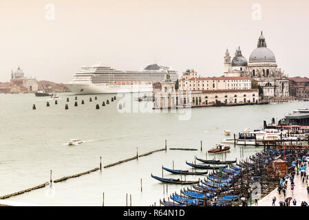 Big white cruise liner coming to Venice, Italy. Showing scale contrast with local architecture and small boats in foreground. Cloudy day with grey sky - Stock Photo