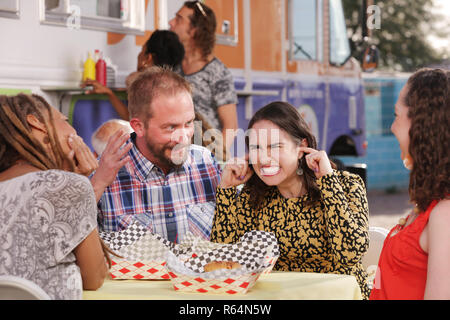 Woman braces herself as friends argue during lunch - Stock Photo