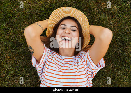 Top view of a happy young girl in summer hat laying on a grass, grimacing - Stock Photo