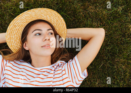 Top view of a lovely young girl in summer hat laying on a grass, grimacing - Stock Photo