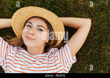 Top view of a cute young girl in summer hat laying on a grass, grimacing - Stock Photo