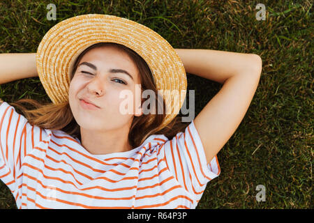 Top view of a funny young girl in summer hat laying on a grass, grimacing - Stock Photo