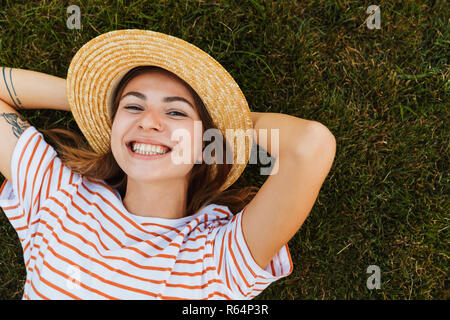 Top view of a smiling young girl in summer hat laying on a grass, grimacing - Stock Photo