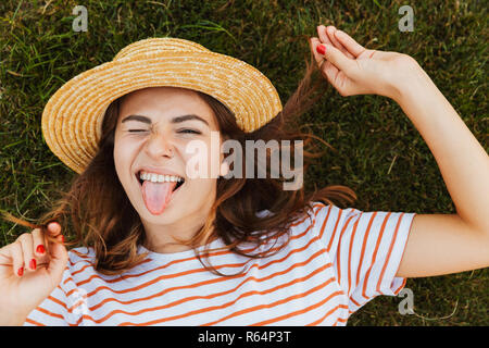 Top view of a lovely young girl in summer hat laying on a grass, grimacing, winking - Stock Photo