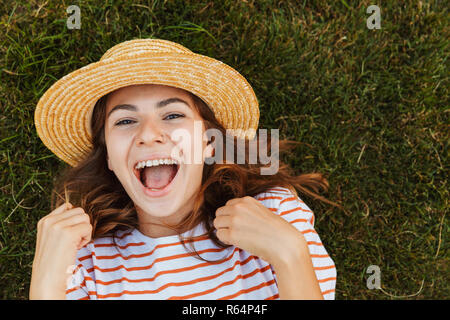Top view of a cheery young girl in summer hat laying on a grass, grimacing - Stock Photo
