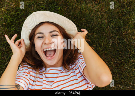 Top view of a joyful young girl in summer hat laying on a grass, grimacing - Stock Photo