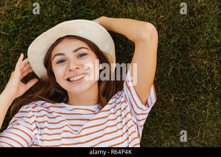 Top view of a delighted young girl in summer hat laying on a grass, grimacing - Stock Photo