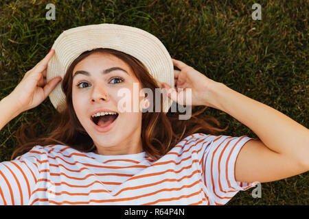 Top view of an excited young girl in summer hat laying on a grass, grimacing - Stock Photo