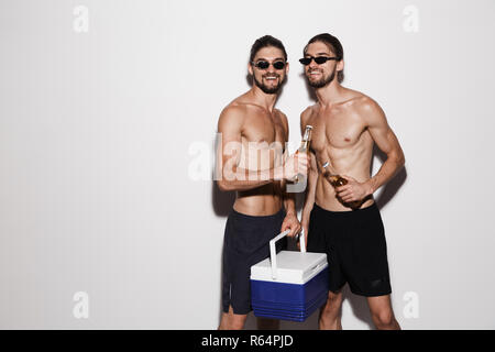 Portrait of a two laughing muscular shirtless twin brothers isolated over gray background, holding beer bottles and cooler fridge - Stock Photo