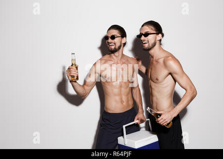 Portrait of a two laughing muscular shirtless twin brothers isolated over gray background, holding beer bottles and cooler fridge, looking away - Stock Photo