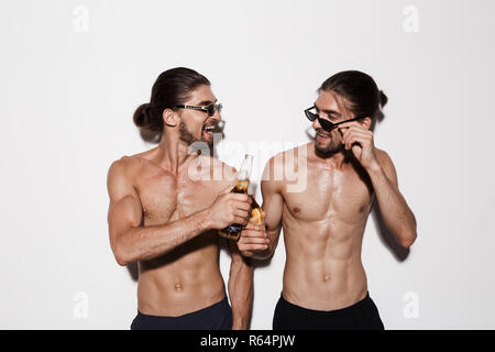 Portrait of a two laughing muscular shirtless twin brothers isolated over gray background, toasting with beer bottles - Stock Photo