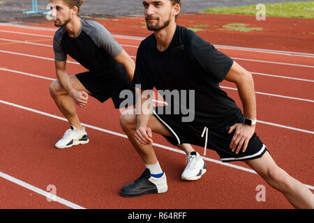 Cropped photo of handsome young two twins brothers make stretching exercises outdoors. - Stock Photo