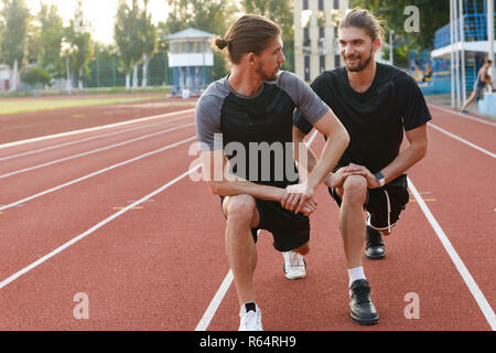 Image of handsome young two twins brothers sportsmen make stretching exercises outdoors. - Stock Photo