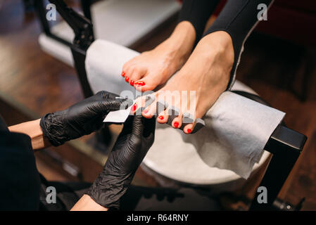 Pedicure master in black gloves polishes nails with a file, female