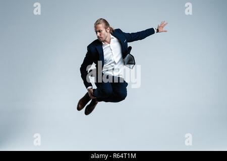 Young successful businessman in suit rejoicing, jumping over white background. - Stock Photo