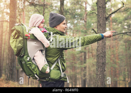father with baby in child carrier on a hike in the woods - Stock Photo