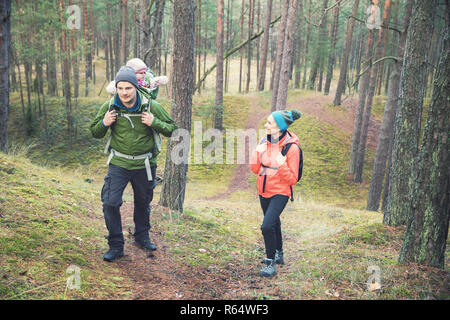 family on a hike in the forest with baby in child carrier on father's back - Stock Photo
