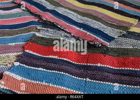 Traditional rustic striped multi-colored rug. Bright textile. Village eco concept. Selective focus - Stock Photo